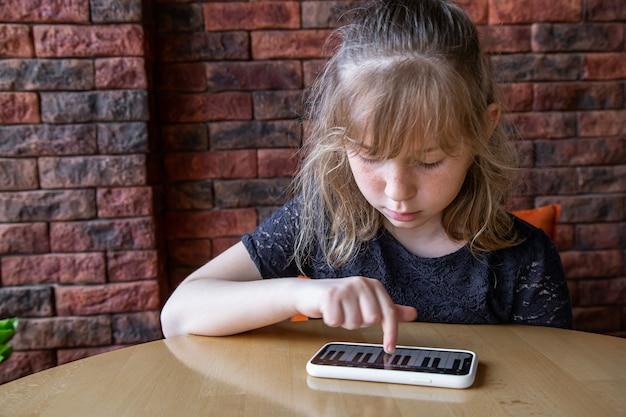 小さな女の子は、携帯電話のピアノの助けを借りて、遊び心のある方法で音符を学びます