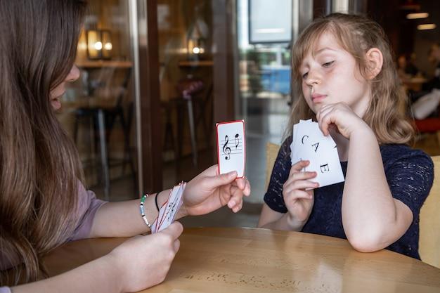 小さな女の子は、特別な音楽カードの助けを借りて、遊び心のある方法で音符を学びます。