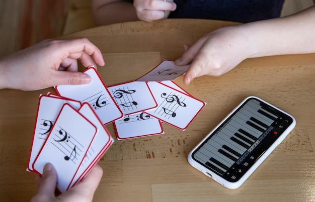 小さな女の子は、特別な音楽カードの助けを借りて、遊び心のある方法で音符を学びます