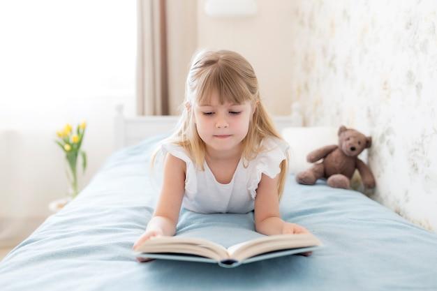 어린 소녀가 세련된 침실의 침대에 누워 숙제를하며 파란색 책을 읽습니다. 교육, 홈 스쿨링 개념. 침대 근처 꽃병에 노란 튤립