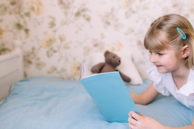 小さな女の子がスタイリッシュな寝室のベッドに横になり、宿題をしながら青い本を読みます。教育、ホームスクーリングの概念