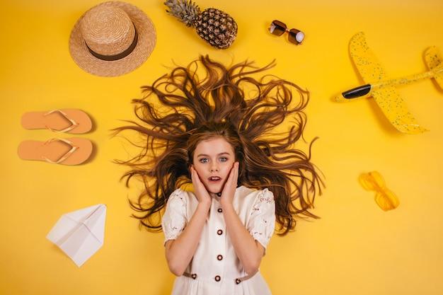 少女は黄色の背景にあり、彼女の周りにはスリッパ、パイナップル、帽子、飛行機があります。