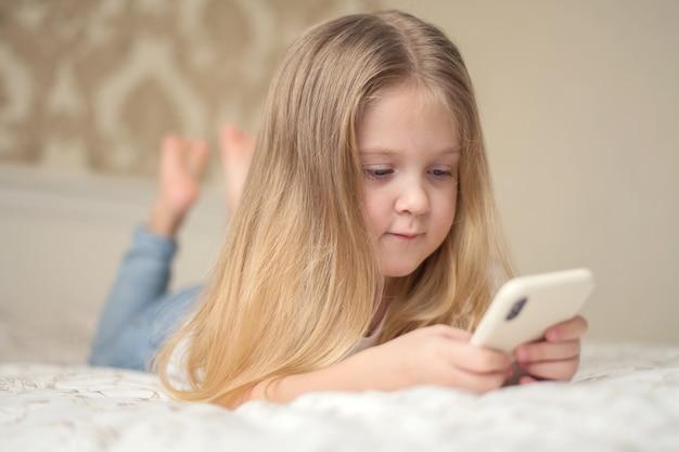 어린 소녀가 침대에 누워 전화 소셜 인터넷에서 재생합니다.