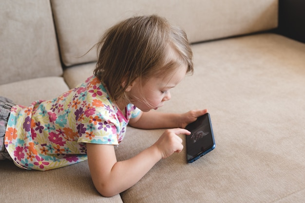 Маленькая девочка лежит на диване и смотрит в телефон
