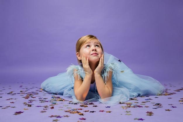 어린 소녀가 색종이 조각으로 바닥에 누워 보라색을 찾습니다.