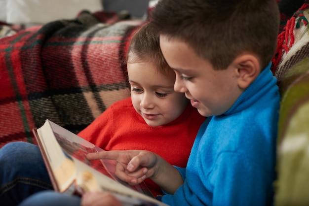 Маленькая девочка смотрит на фотографию в семейном альбоме, а ее брат что-то показывает ей