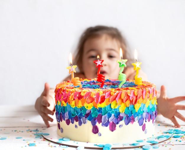 小さな女の子が美しいバースデーケーキを見ています。誕生日のサプライズコンセプト