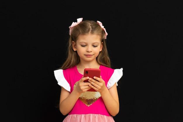 Маленькая девочка смотрит на свой телефон.