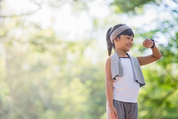 어린 소녀는 공원에서 훈련 후 스마트 시계를 살펴봅니다. 건강한 개념입니다. 여성 후