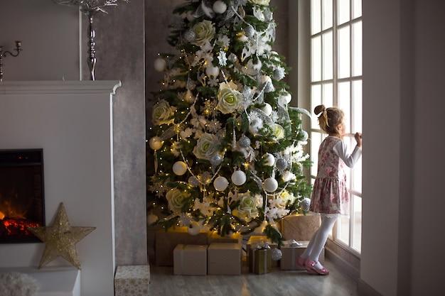小さな女の子がクリスマスツリーの近くの大きな窓の外を見ています。家の居間で奇跡のクリスマスホワイトの装飾を待っています。新年、おとぎ話と魔法、子供の夢