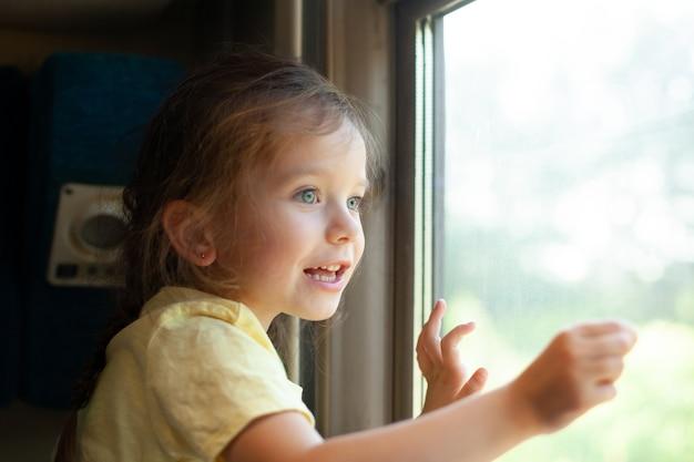 어린 소녀가 흥미를 가지고 기차 창 밖을 내다본다 아이와 함께 여행