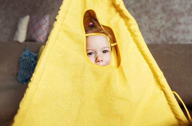 어린 소녀가 천막 창밖을 내다 보며 집에서 소파에서 놀아요. 집에서 어린이 게임.