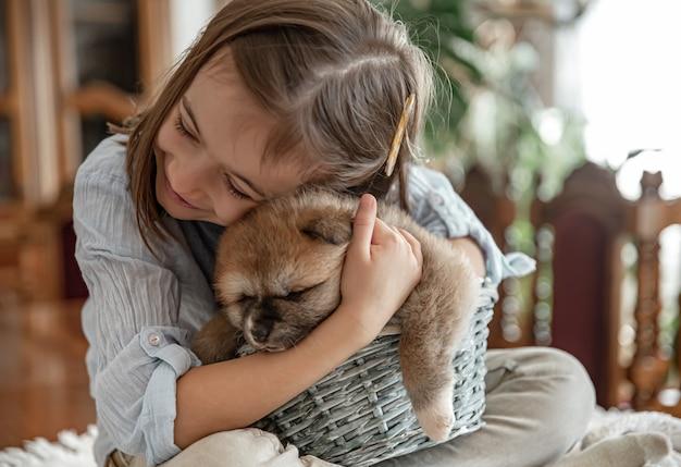 어린 소녀는 어린 강아지를 사랑하고 포옹합니다.