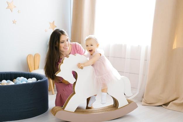ピンクのドレスを着た1歳の少女が木の馬に座って、幸せで笑顔です。