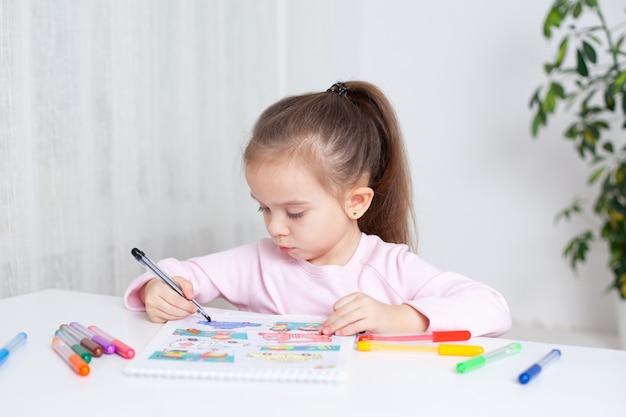 45세 소녀가 앨범 컬러 마커에 열심히 그림을 그립니다.