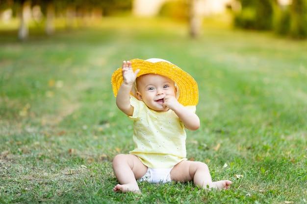 8ヶ月の小さな女の子が夏に黄色の夏のドレスと帽子で緑の芝生に座っています。