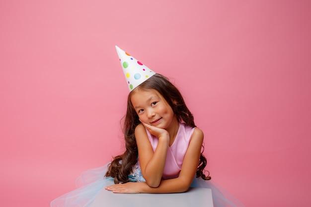 頭に帽子をかぶったアジア風の少女がピンクで誕生日を祝う