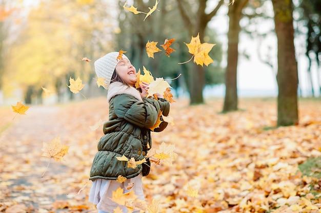 目を閉じて笑顔で5歳の少女が秋の公園で落ち葉をキャッチ