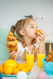 白いtシャツを着た7歳の少女が台所のテーブルに座っています。マンダリンタンジェリンと焼きたてのクロワッサンとチョコレートが入っています