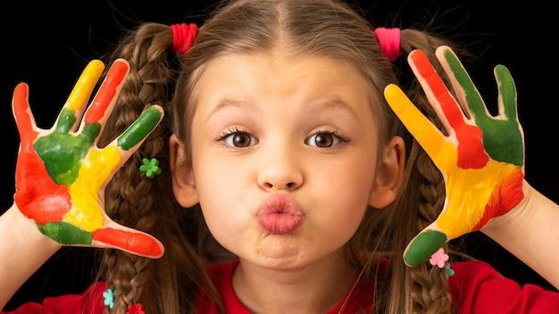 Маленькая девочка на черном фоне замазана краской.
