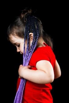 Afro-pigtails가있는 검은 배경에 어린 소녀, 탄성 밴드로 인공 도금하고 귀여운