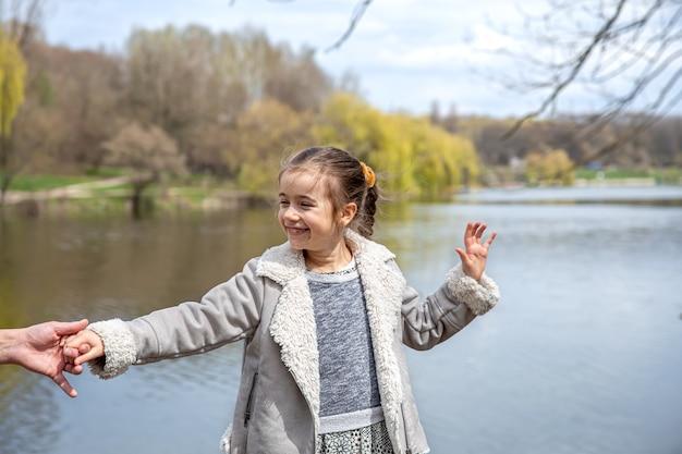 이른 봄에 공원을 산책하는 어린 소녀가 아빠의 손을 잡고 있습니다.