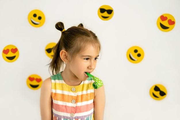 다양한 감정 상태의 이모티콘이 있는 흰색 배경에 있는 어린 소녀는 사랑에 슬픈 기쁨 행복