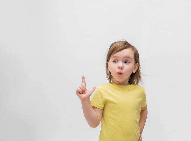Маленькая девочка на белом пространстве указывает вверх. милая девушка с распущенными волосами в желтой футболке. маленькая девочка удивлена. свободное место