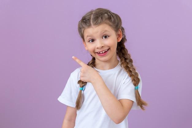 외진 배경에 있는 어린 소녀는 미소를 지으며 손가락으로 옆을 가리킵니다.