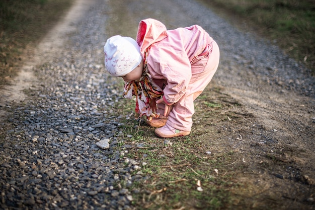 Маленькая девочка на проселочной дороге с камнями. ребенок поднимает камень в форме сердца.