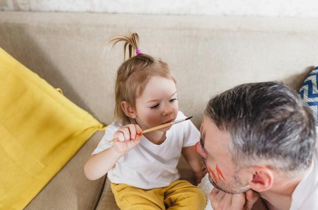 ソファの上の小さな女の子が一緒に家族のゲーム中に父親の顔を注意深くペイントします