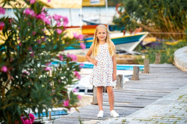 ダルヤン市の白いサンドレスで川沿いの堤防にいる少女。七面鳥