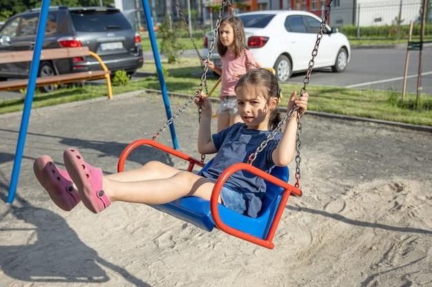 Маленькая девочка на детской площадке катается на качелях.
