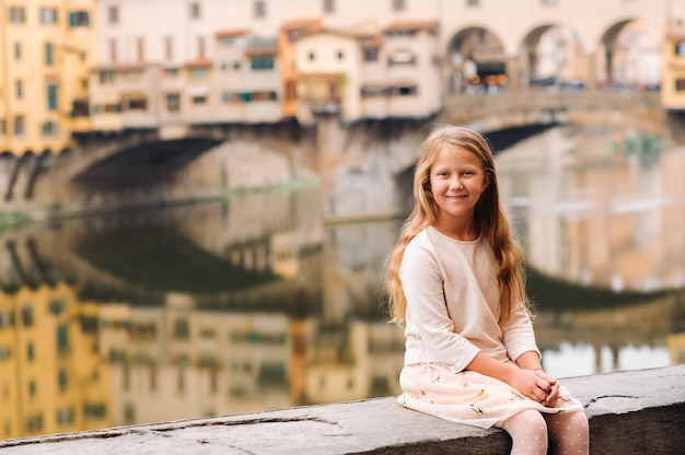 フィレンツェのヴェッキオ橋の小さな女の子。イタリアの家族の散歩。トスカーナ。