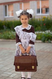 Маленькая девочка на улице в винтажной униформе с портфелем стоит возле школы