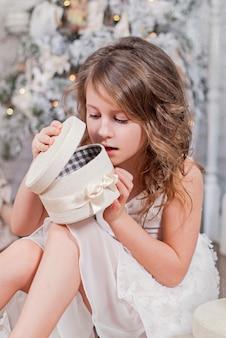 Маленькая девочка открывает коробку с рождественским подарком и заглядывает в нее.