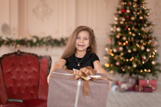 小さな女の子がサンタさんからクリスマスプレゼントを開けます。クリスマスの物語。幸せな子供時代。