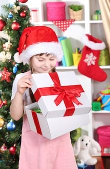 小さな女の子がお祝いに飾られた部屋で贈り物を開きます