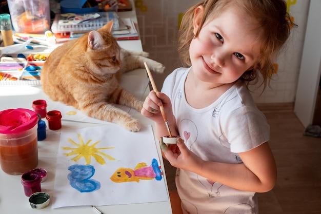小さな女の子が太陽を描き、母親が水彩絵の具でテーブルの横に生姜猫が横たわっています。