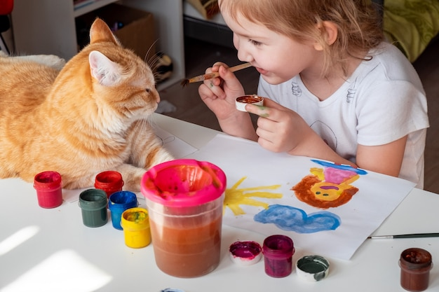 小さな女の子が太陽と母親を水彩で描く