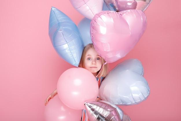 Маленькая девочка выглядывает из-за воздушных шаров. день детей