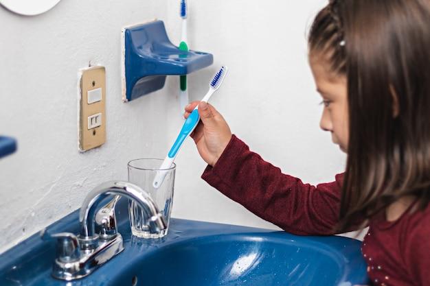 小さな女の子がバスルームのグラスに歯ブラシを置きます