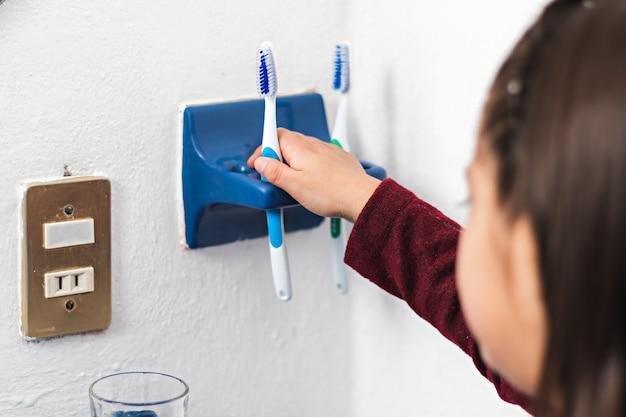 小さな女の子がバスルームの歯ブラシホルダーに歯ブラシを置きます