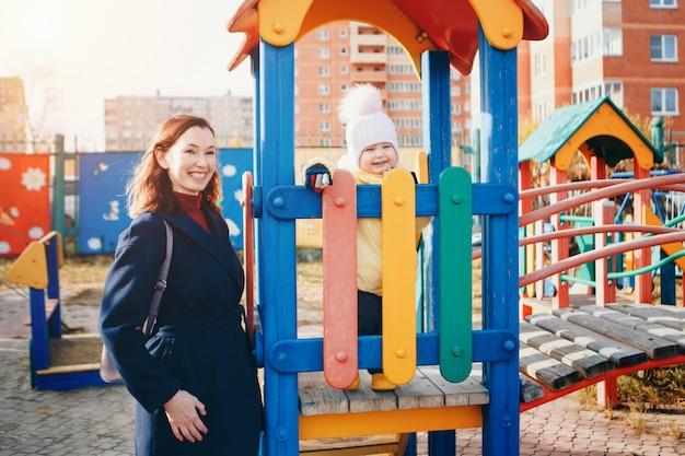 Маленькая девочка играет на детской площадке детского городка. маленький ребенок едет вниз по склону, на карусели, взбирается на канаты. концепция индустрии развлечений, семейный день, детские парки