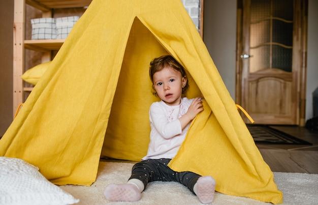 노란색 천막 안에 어린 소녀 놀이