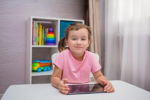 Маленькая девочка играет с планшетом за столом в комнате