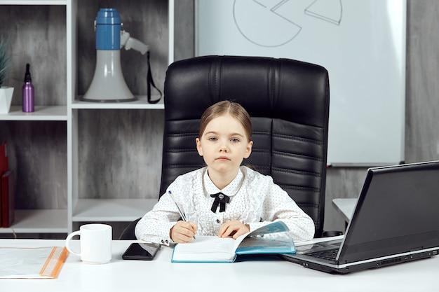 어린 소녀는 사무실의 흰색 책상에서 상사를 묘사합니다.