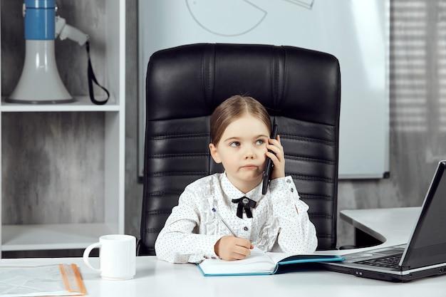 어린 소녀는 휴대 전화로 말하는 상사를 묘사합니다.