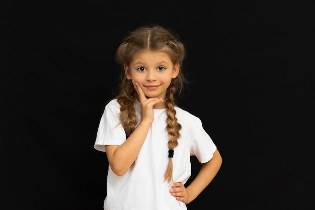 Маленькая девочка позирует на черном фоне.