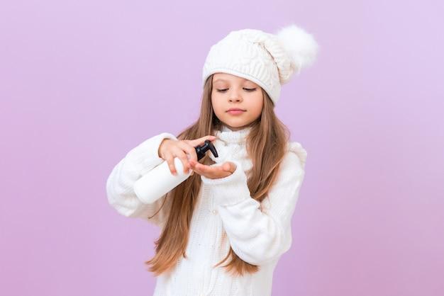 小さな女の子は、孤立したピンクの背景に彼女の手に冬の霜からクリームを注ぐ。